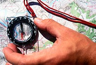 Detail of a hand using a compass on a map