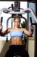 Woman working out by weight lifting on a home gym