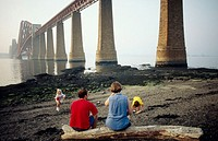 Family by the Forth Bridge. Firth of Forth, near Edinburgh. Scotland