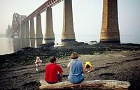 Family by the Forth Bridge. Firth of Forth, near Edinburgh. Scotland