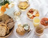 Breakfast table with herb quark roll, muesli, jam, tea