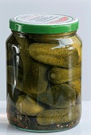 Pickled gherkins in jar on light background
