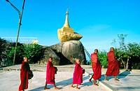 Buddhist monks collecting food. Kyaiktiyo Pagoda (Golden Rock Pagoda) at dusk. Mon State. Myanmar (Burma)
