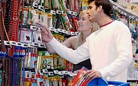 Couple looking at electronic price displays at the pets section of Eroski shopping center. These displays are updated by remote control. Urbil. Usurbi...