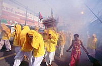 Firecrackers are thrown at religious procession to scare away evil spirits. Vegetarian Festival. Phuket. South Tahiland