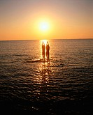 Two silhouettes at shoal in sunset