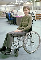Disabled woman in a wheelchair works in an office