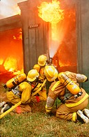 Firefighting. Firefighter wear face masks and wear oxygen cylinders to allow normal breathing in the presence of the thick black smoke. Anacortes, Was...