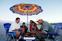 A hispanic family plays and watches backgammon under an umbrella on Miami Beach.