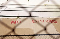 'No diving'painted on pavement next to a swimming pool. Viewed through a fence. Illinois. USA