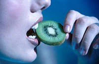 womans mouth eating kiwi fruit