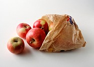 Apples spilling out of paper sack