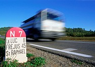 Fast moving vehicle on road, signs for locations in South France