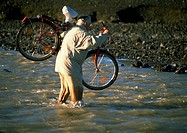 Iceland, man carrying bicycle through water