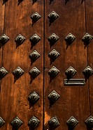 Wooden door with brass studs, close-up