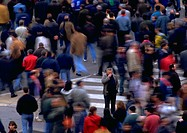 Crowd walking by man standing in opposite direction, blurred motion