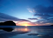 New Zealand, Mahia Beach, ocean sunset with cliff in background