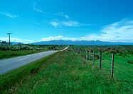 New Zealand, road going through grassy rural area, mountain range in distance