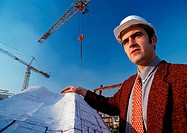 Man wearing hard hat, holding blueprint, cranes in background, low angle view