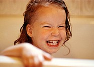 Girl with wet hair holding edge of bathtub, smiling