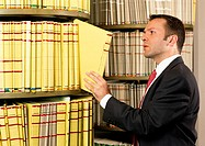 Man taking document from shelf