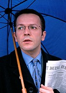 Man holding umbrella and newspaper, portrait