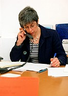 Woman sitting at desk, telephoning
