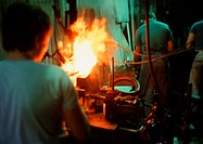 Man working in glass factory, rear view