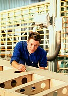 Man in coveralls behind woodwork, looking into camera, head and shoulders