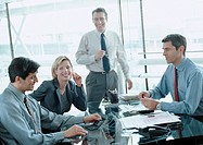 Four business people in conference room, blurred