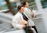 Two businessmen walking outside, blurred motion
