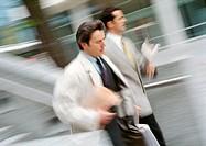 Two businessmen walking outside, blurred motion