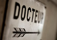 'Doctor' text in French on sign with arrow, close-up
