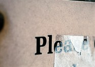 'Please' text printed on paper and partially obscured, close-up