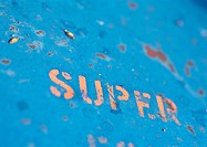 'Super' text stenciled on rusty surface, close-up