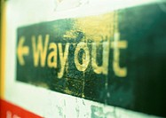 'Way out' text and arrow on sign, close-up