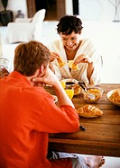 Couple sitting at table, having breakfast