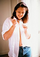 Woman wearing jeans and open shirt, standing, eating yogurt, close-up