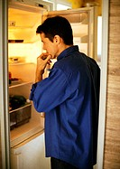 Man standing in front of open refrigerator, side view