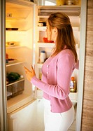Woman standing in front of open refrigerator, side view