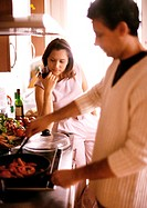 Man cooking in blurred foreground, woman holding glass in background