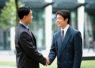 Two men shaking hands, outside