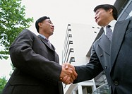 Two men shaking hands, low angle view