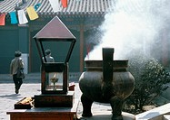 China, Hebei Province, Beijing, censer letting off smoke in courtyard, people in background