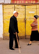 China, Xingjiang Province, Turpan, man in street walking with cane, blurred motion