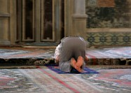 Israel, Jerusalem, Muslim man praying in mosque, rear view, blurred