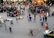 Groups of people gathered in a city square, elevated view, blurred motion
