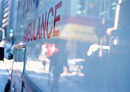 Street scene reflected on white ambulance, composite, close-up