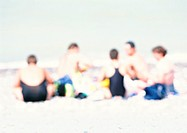 Group of people sitting on sand at the beach, blurred