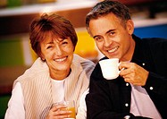 Man and woman sitting together smiling, man holding mug, close up